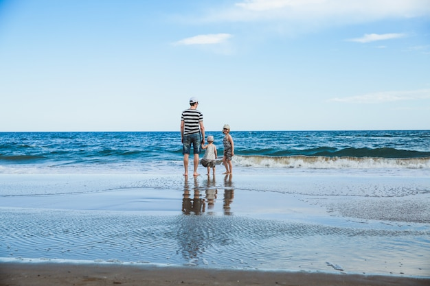 父と2人の娘、地中海のビーチに立っています。 Premium写真