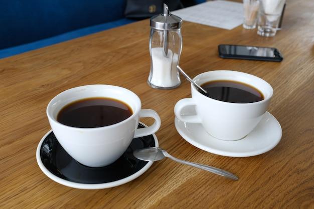木製のテーブル、朝のコーヒーに黒のコーヒー2杯。 Premium写真