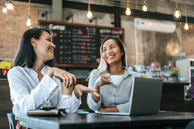 座っているとコーヒーショップでラップトップで働く2人の女性 無料写真