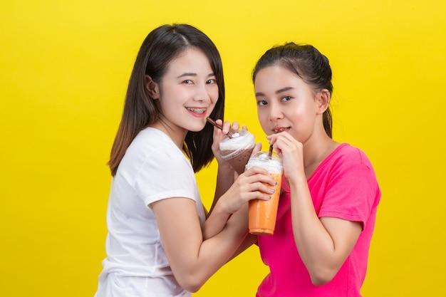 2 азиатских женщины выпивая замороженный чай молока и замороженное какао на желтом цвете. Бесплатные Фотографии