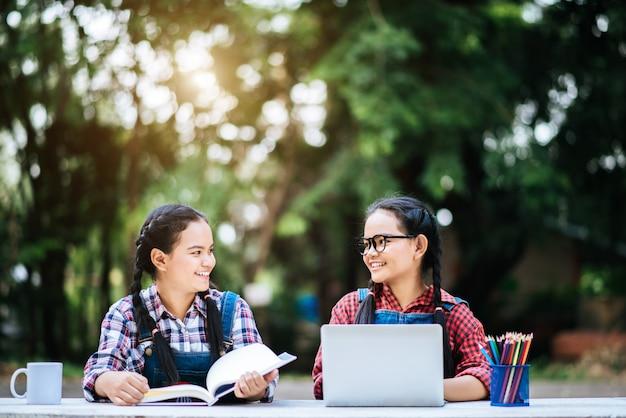 公園内のラップトップとオンラインで一緒に勉強している2人の学生 無料写真