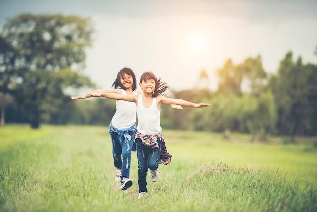 2人のかわいい女の子が緑の草で走っています。親友。 無料写真