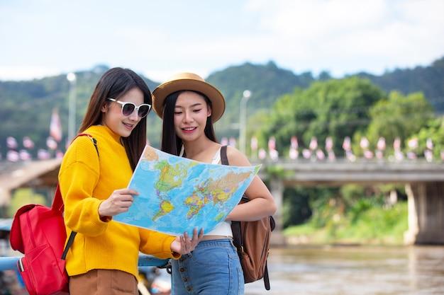 2人の女性観光客が場所を見つけるために地図を持っています。 無料写真