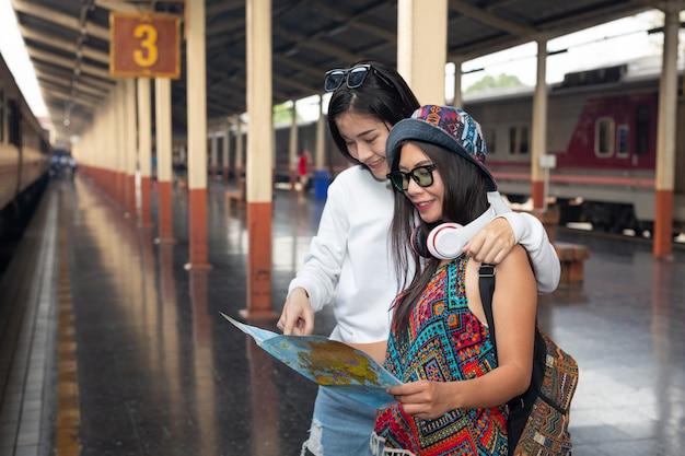 電車を待っている間、2人の女性が地図を持っています。観光の概念 無料写真