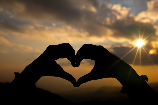 日の出背景を持つ2つの手からハート形。 無料写真