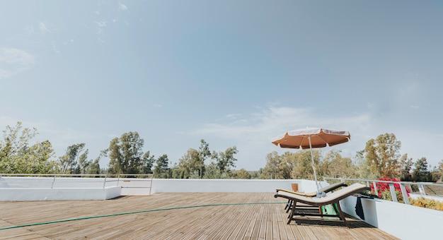 太陽の下で2つのサンベッドと青い空と木製の高原のサンシェード Premium写真
