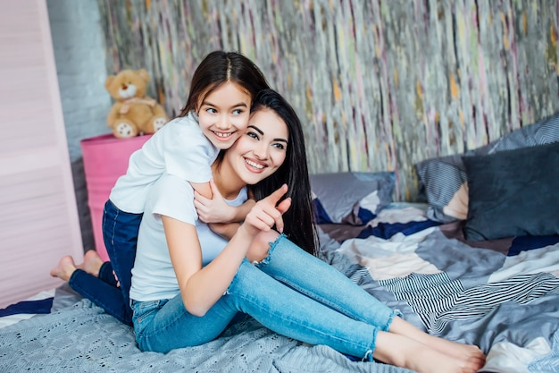 部屋のベッドの上に座っている2人の幸せな妹の画像。 Premium写真