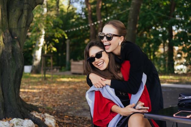 彼女の友人を抱き締める少女。肖像画公園の2つのガールフレンド。 無料写真