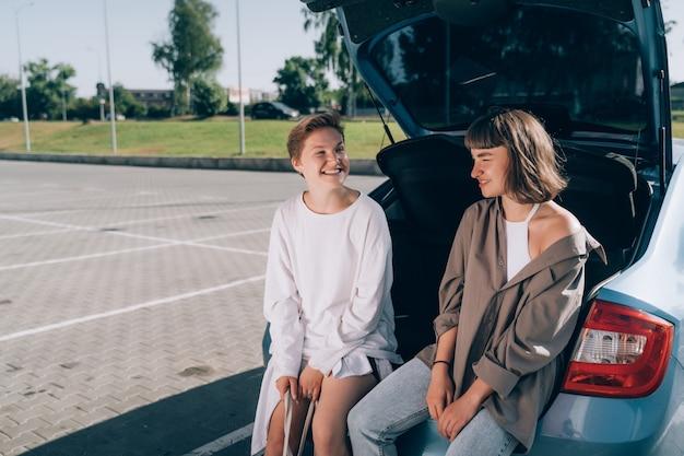 カメラにポーズをとって、開いているトランクの駐車場にいる2人の女の子。 無料写真