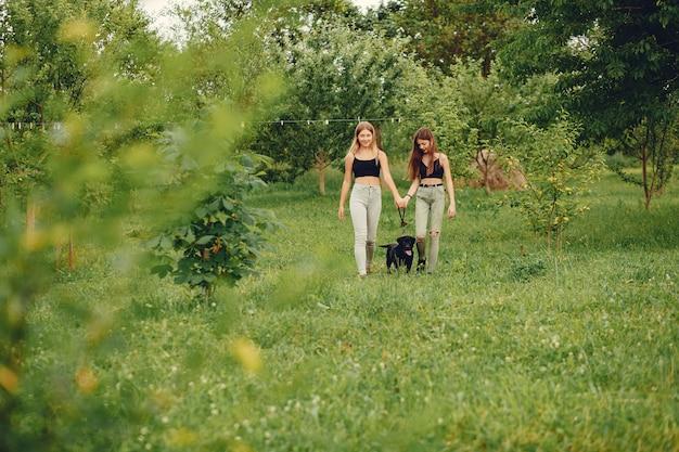 犬と一緒に夏の公園で2人のかわいい女の子 無料写真