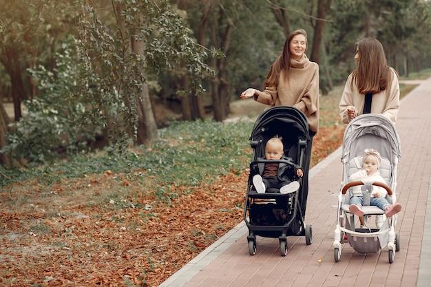 馬車で秋の公園を歩く2人の若い母親 無料写真