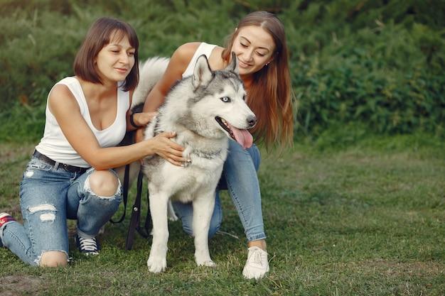 春の公園でかわいい犬と遊ぶ2人の女性 無料写真