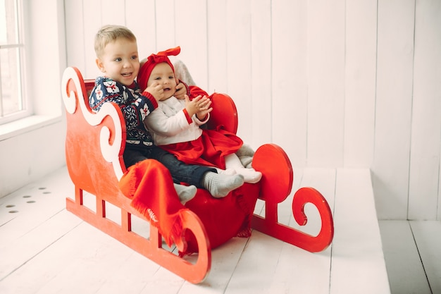クリスマスの飾りに座っている2人のかわいい子供 無料写真