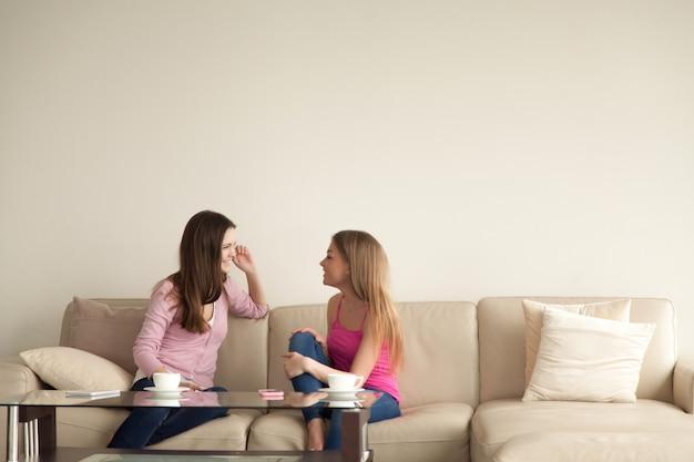 2人の若いガールフレンドが家でのんびりして会話を 無料写真