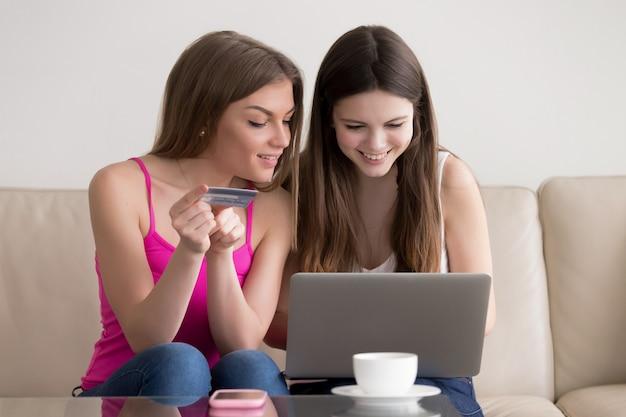 インターネットで商品を注文する2人の幸せなガールフレンド 無料写真