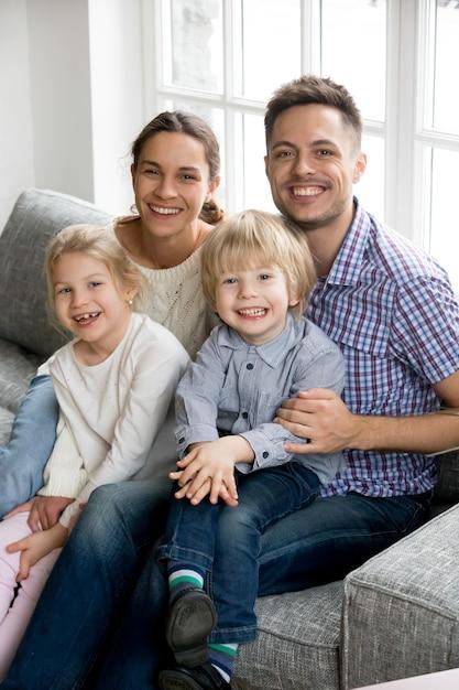 2人の子供のための新しい幸せな親、家族の垂直方向の肖像画 無料写真