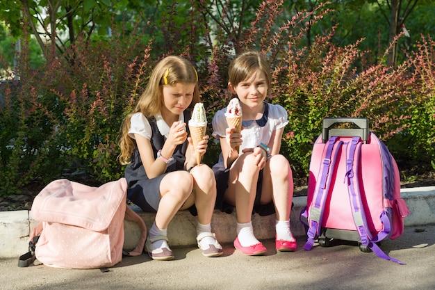 アイスクリームを食べる2つのガールフレンド女子学生の肖像画 Premium写真