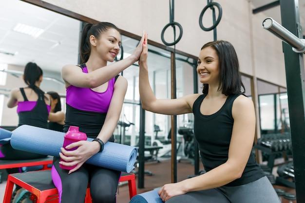 スポーツマットと話している2人の若い笑顔フィットネス女性 Premium写真