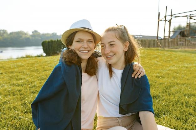 2人の若い笑顔のガールフレンドに座って抱きしめる Premium写真