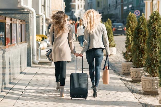 通りを歩いているスーツケースを持つ2人の若い女性 Premium写真