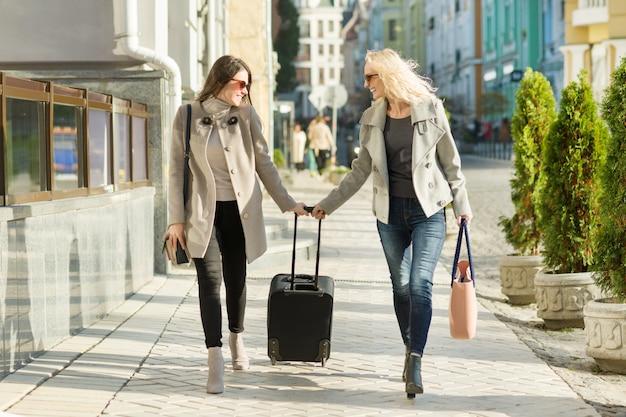 スーツケースと2人の若い笑顔の女性 Premium写真
