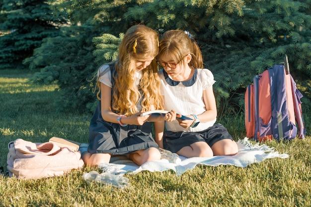公園の草原に座って学習2つの小さなガールフレンド女子高生 Premium写真