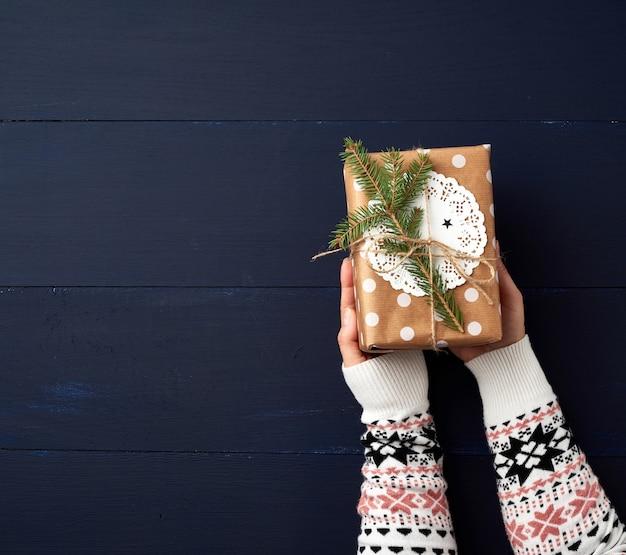 2つの女性の手が青い木製の紙の閉じた箱を保持します。お祭りのコンセプト Premium写真