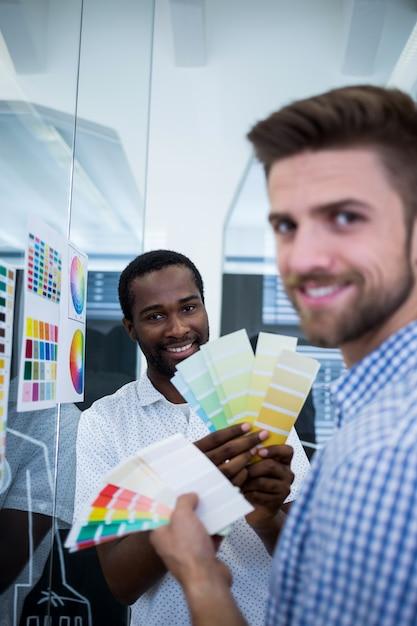色見本を固定している2つの男性のグラフィックデザイナー 無料写真