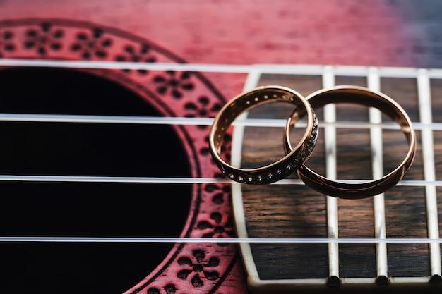 2つの金の結婚指輪はギターの弦の上にあります。 Premium写真