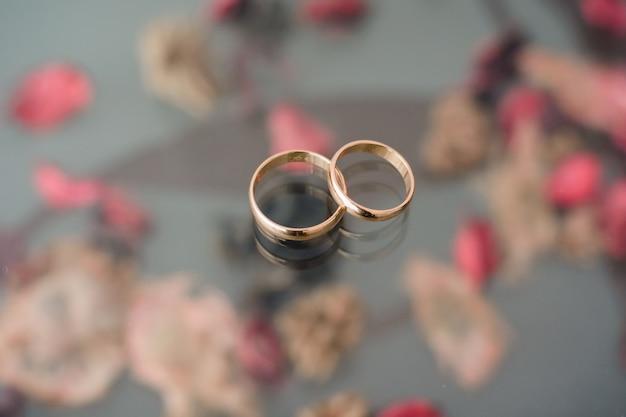 2つの伝統的な結婚式の金の婚約指輪があります。 Premium写真