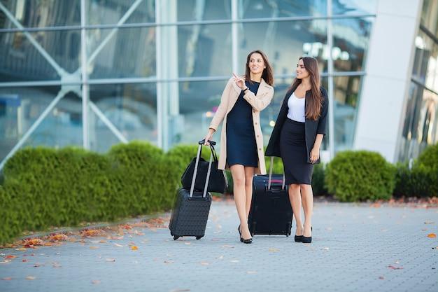 一緒に海外旅行、空港でスーツケースの荷物を運ぶ2つの幸せな女の子 Premium写真