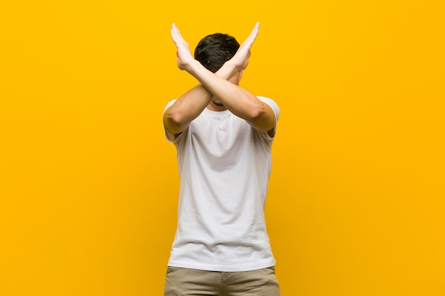 ヒスパニック系のカジュアルな若者が2本の腕を組んで、拒否の概念を維持します。 Premium写真