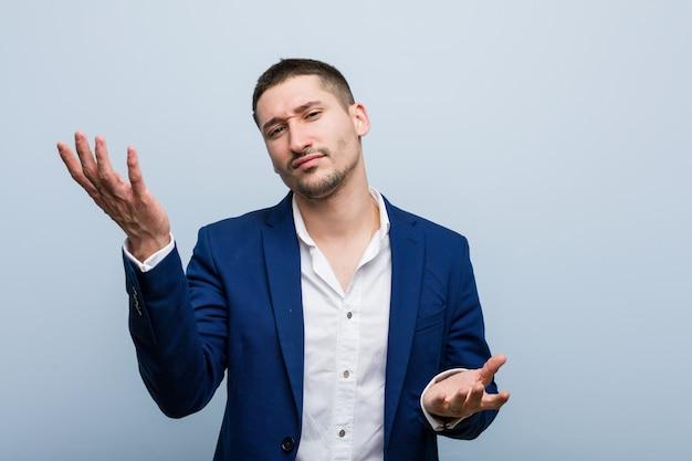 Человек молодого дела кавказский сомневаясь между 2 вариантами. Premium Фотографии