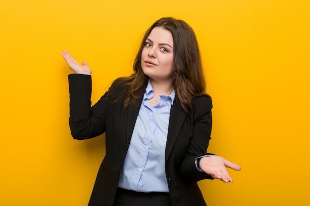 2つのオプションの間を疑っている若いプラスのサイズの白人ビジネス女性。 Premium写真