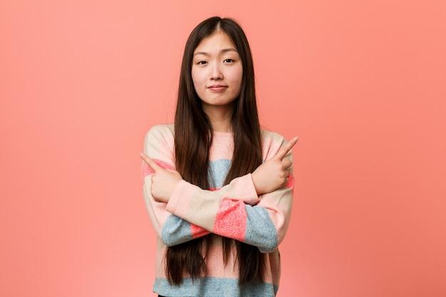 若いクールな中国人女性は横向きのポイント、2つのオプションのいずれかを選択しようとしています。 Premium写真