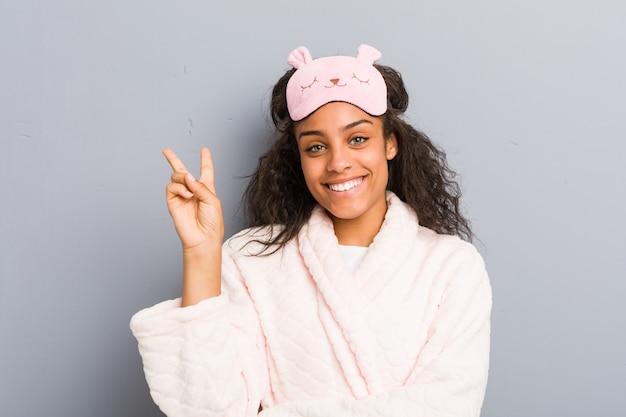 パジャマと睡眠マスクを身に着けている若いアフリカ系アメリカ人女性は、指で2番を示します。 Premium写真