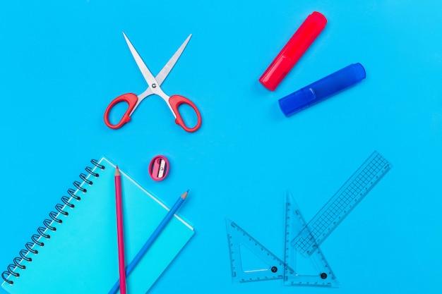 鉛筆、赤いはさみ、ピンクの鉛筆削り、透明な定規、2つの赤と青のマーカーで青の上に横たわる黒いリングの青いノート。 Premium写真