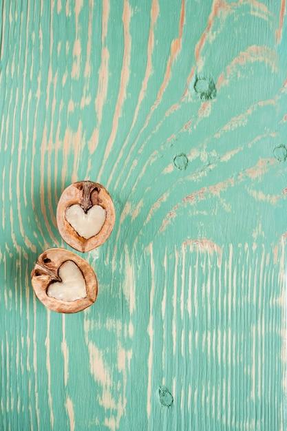 心としてのクルミの2つの半分は、縞模様と波状の汚れと明るい緑の木製テーブルの上に横たわっています。 Premium写真