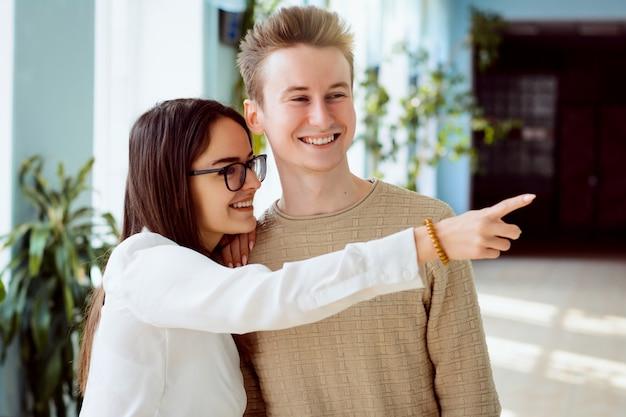 若い女性と男性の学生は、大学の廊下で何らかのうわさ話をし、いじめています。クラスメートについての秘密を共有している2人の友人が、休憩中に彼女を指さして笑う Premium写真