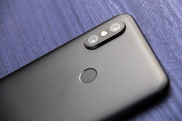 2台のカメラと指紋リーダーを備えた黒いスマートフォン。青い木製テーブルにデュアルカメラのスマートフォンをクローズアップ Premium写真