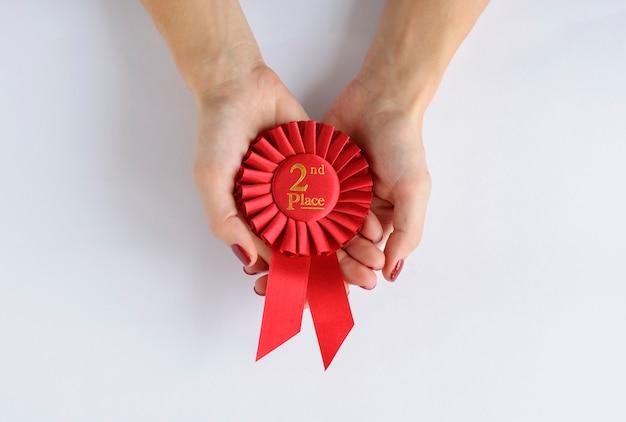Женщина, держащая красную розетку победителей 2-го места Premium Фотографии