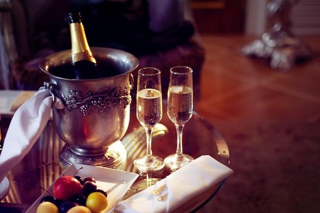 静物、ロマンチックなディナー、グラス2杯、アイスバケットにシャンパン。お祝いや休日 Premium写真