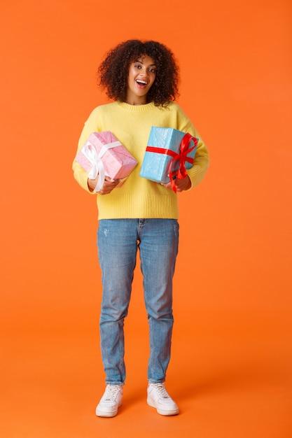 フルレングスの垂直ショットは、かわいい幸せなアフリカ系アメリカ人女性が休日の贈り物を受け取って興奮し、楽しませて喜んで立って、2つの包まれたプレゼントを保持している、オレンジ Premium写真