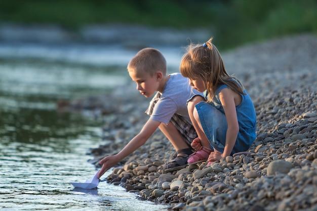 2人のかわいい金髪の子供、男の子と女の子の川の土手で水ホワイトペーパーボートを送信します。喜びと幸せな子供時代と屋外活動の概念のゲーム。 Premium写真