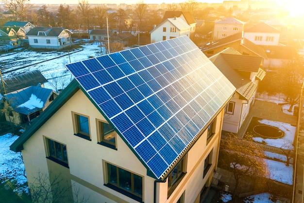 屋根の上の青い光沢のある太陽光発電システムと新しいモダンな住宅2階建て家コテージの空中のトップビュー。再生可能な生態学的なグリーンエネルギー生産の概念。 Premium写真