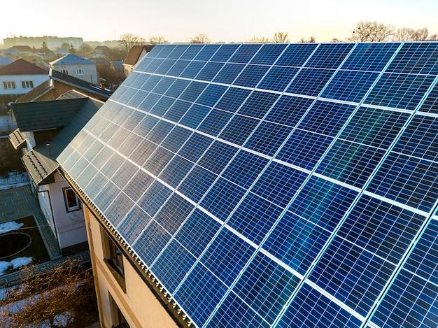 屋根の上の青い光沢のある太陽光発電システムと新しいモダンな2階建ての家のコテージの空撮。再生可能な生態学的なグリーンエネルギー生産の概念。 Premium写真