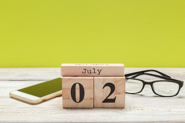 2 июля деревянный, квадратный календарь. деловая поездка или планирование отпуска Premium Фотографии