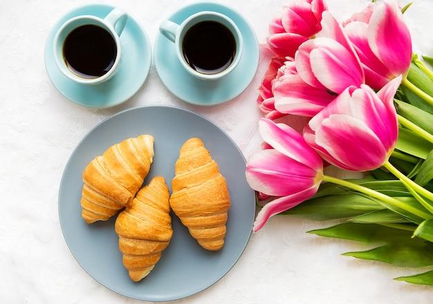 コーヒー2杯、クロワッサン、ピンクのチューリップの花束、美しい朝 Premium写真