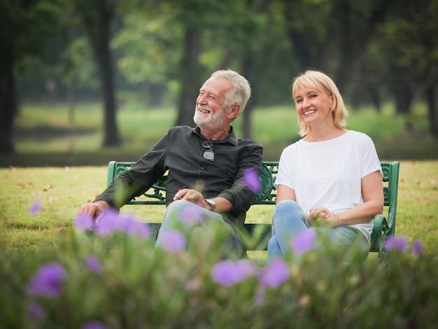 2人の幸せな先輩退職男と女は座っていると公園で話しています Premium写真