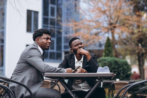 カフェの外に座っている2つのアフリカの実業家 無料写真
